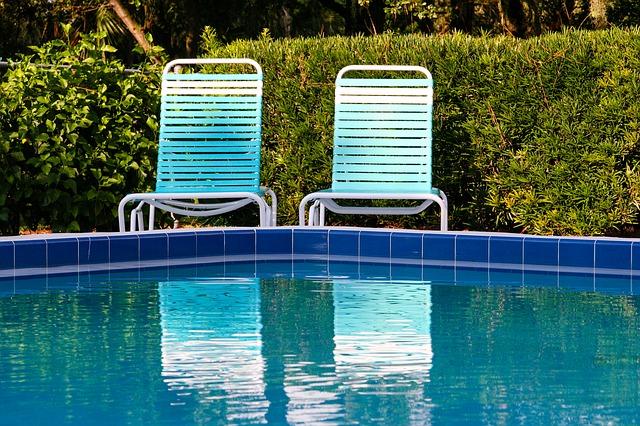 Křišťálově modrý bazén a za ním dvě bílé židličky u živého plotu.jpg